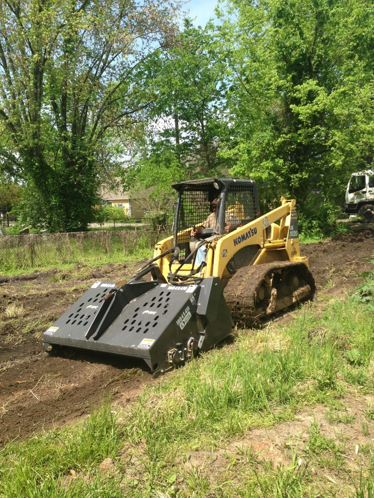 Acadia Landscaping Company removes debris from the soil.