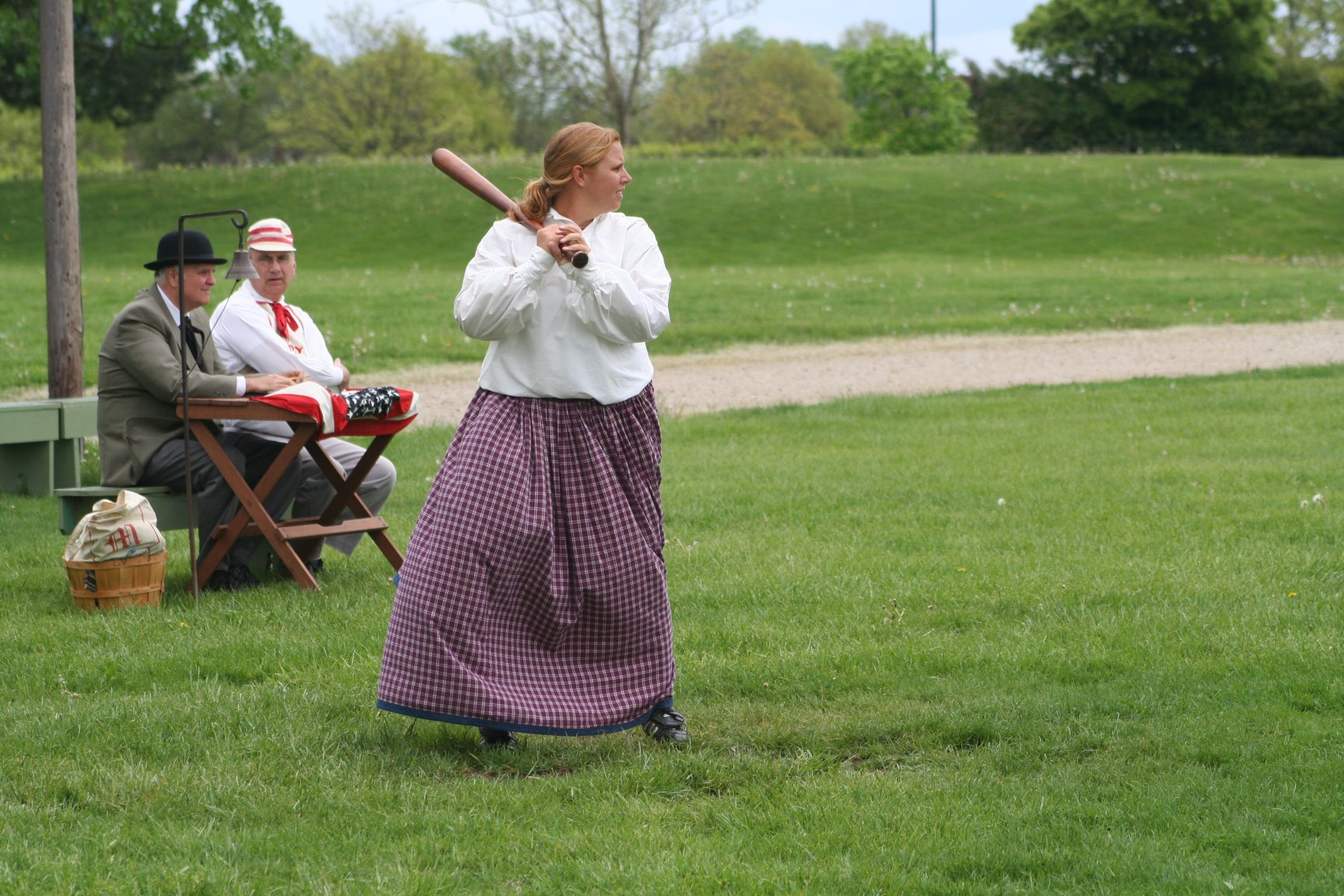 Ohio Village Lady Diamond batter with seated umpire looking on. The Lady Diamonds are an all-female team.