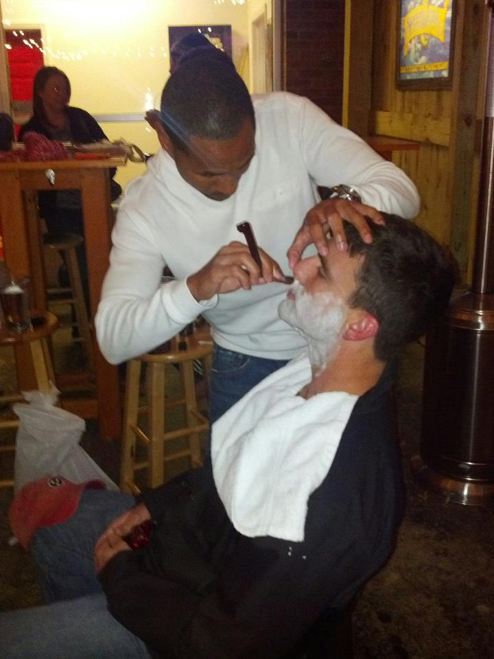"""Marcus D. Blair shaves Mark Lane on Vic's patio during day one of """"No-Shave"""" November."""